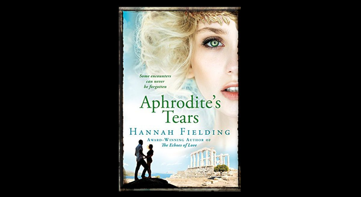 This is the book cover for Hannah Fielding's Aphrodite's Tears. In the foreground are a man and a woman, silhouetted in front of ruins. In the background is a woman's face, half-cut off by the edge of the book. She has blue eyes and blond hair. Her lips are parted.