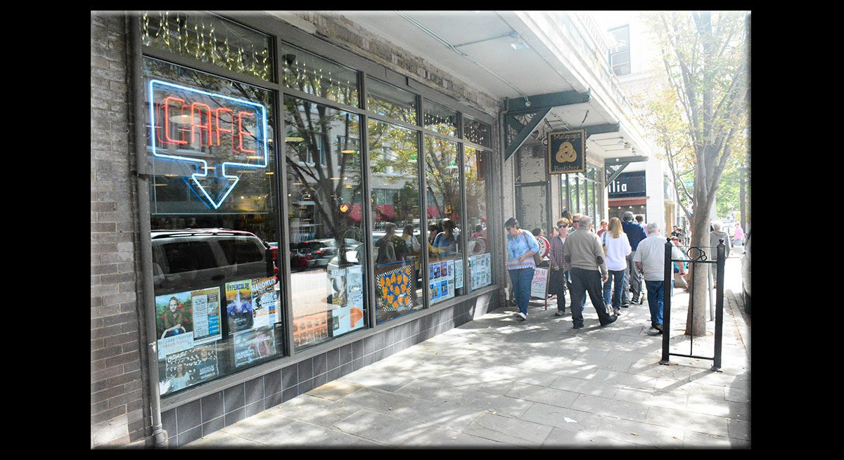 """This is an outdoor shot of the sidewalk and storefront of Malaprop's Bookstore in Asheville. There are bookish posters in the window and a sign that reads """"CAFE"""" in bright red letters, with a blue arrow pointing down."""